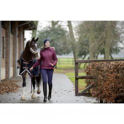 Ridjacka morello druvfärgad på ryttare som leder en häst i en utomhusmiljö utanför ett stall